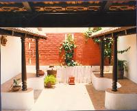 A small 'chettinad' type of courtyard on the first floor of the Dr. Ramamuthi house in Chennai. Traditional wooden pillars and a cement 'thinnai' or seat with the Mangalore tiled roof give it the right ambience.