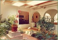 The courtyard on the other side of the corridor. The arches in the corridor are now open thus making it part of the garden as well as the house. The dining room can be seen at the end of the corridor.