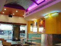 curved ceiling in beaten stainless steel reflecting coloured neon lights in coves