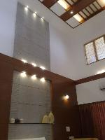 the high ceiling in the living room with the granite cladding and wood paneling.